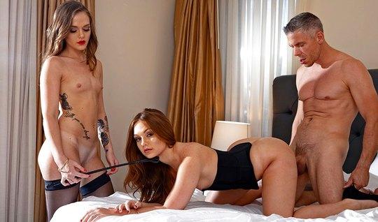 Две молодые девушки и один мужчина в спальне занимаются груп...