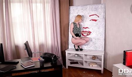Молодая блондинка сосет член через дырку в картине в офисе