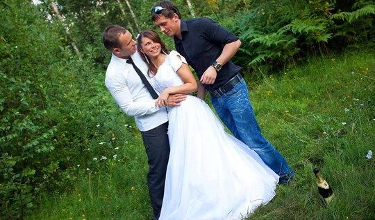 Русская невеста на природе получает от жениха и дружка двойн...